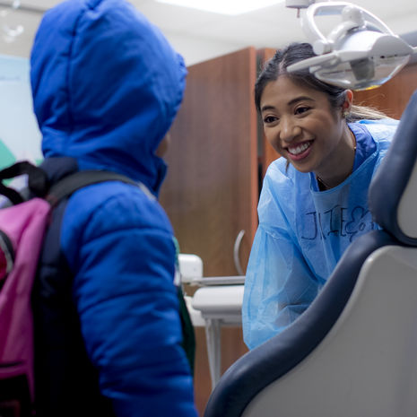 Dental student speaking with a young patient in pediatric dental examination room