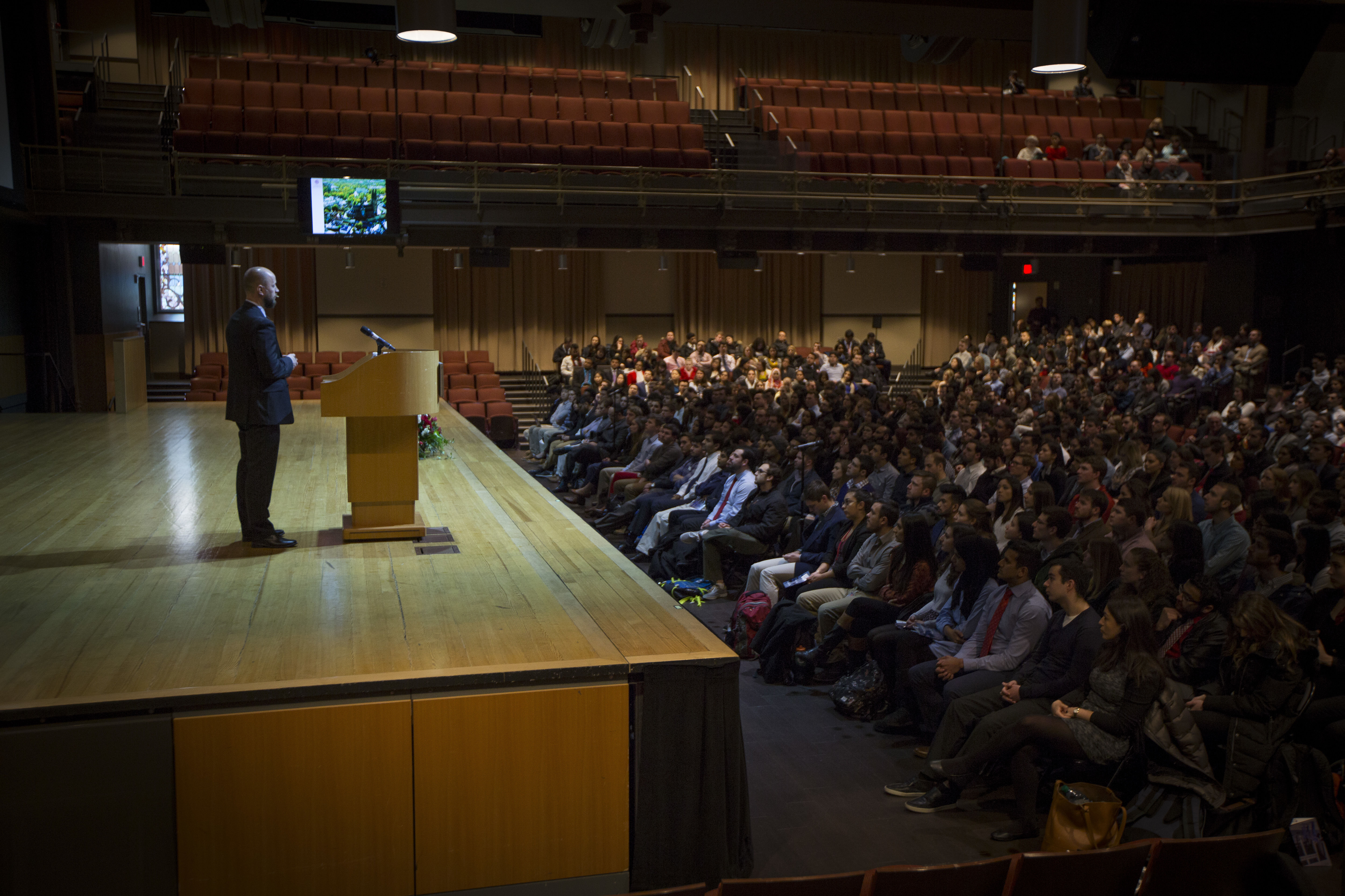 An on-stage speaker addresses the audience during a Research Day event.