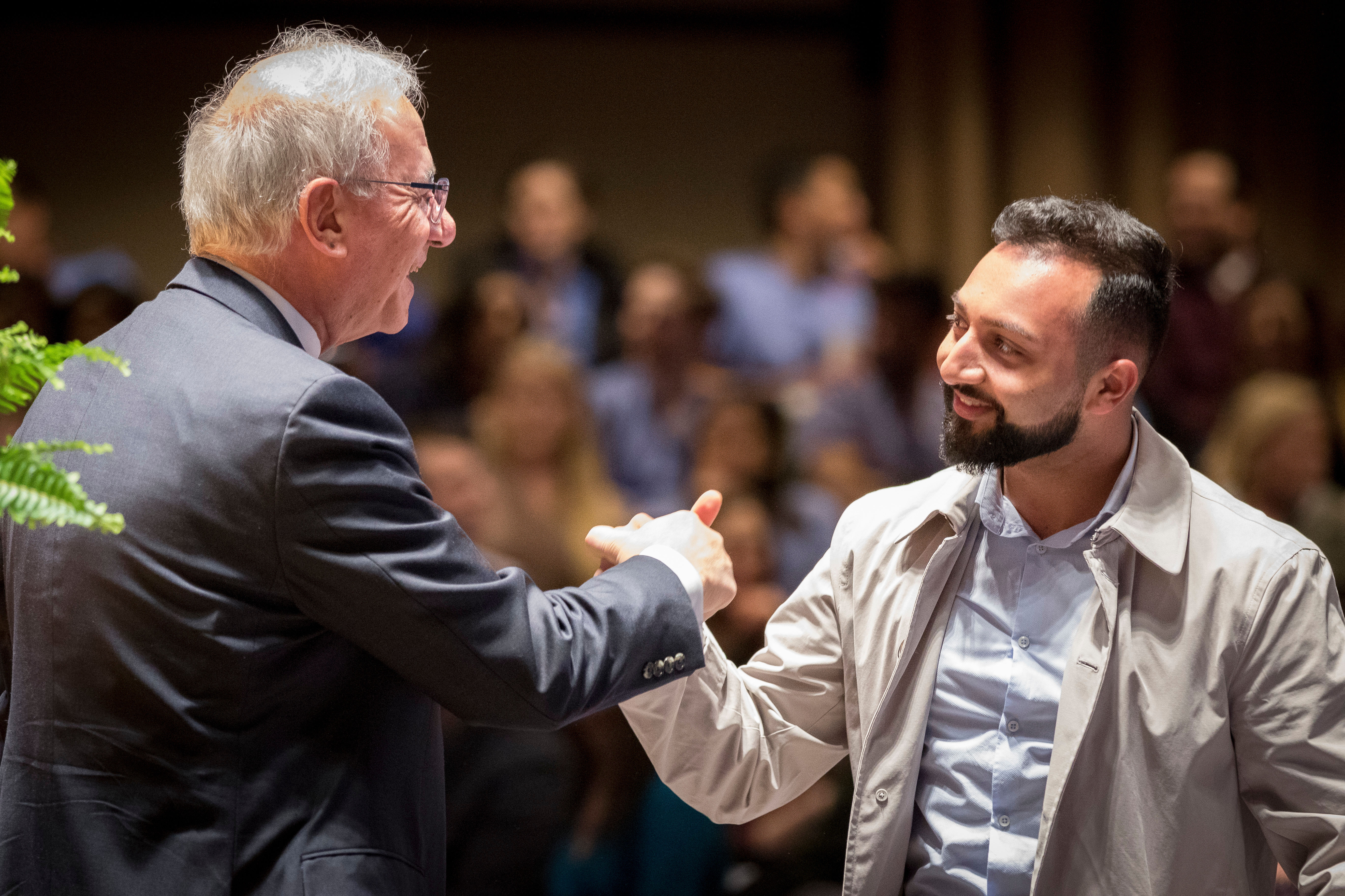 Kornberg Dean Amid Ismail greets a guest during a Research Day event.